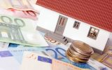 Piccola casa con banconote e monete in euro